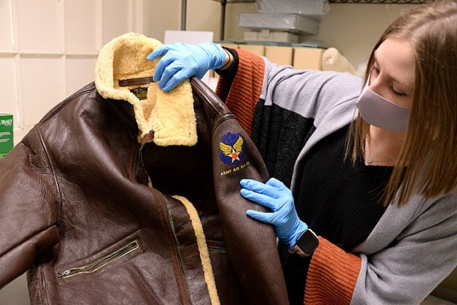 Fayelee Overman, museum technician, holds up a World War II-era Army Air Force mechanic's jacket as she explains its condition and the cleaning of corroded zippers that will need to be done before it can join other early aviation-related items in the recently installed Frontier Flight exhibit Jan. 27 at the Frontier Army Museum. Photo by Prudence Siebert/Fort Leavenworth Lamp