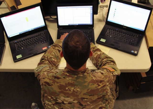 Army Sgt. Kyle Plumley, an intelligence analyst for Joint Force Headquarters, works three laptop computers at Camp Atterbury, Ind. The Army Futures Command is enabling Army personnel at Aberdeen Proving Ground, Maryland, to remotely access classified networks via their commercial internet.