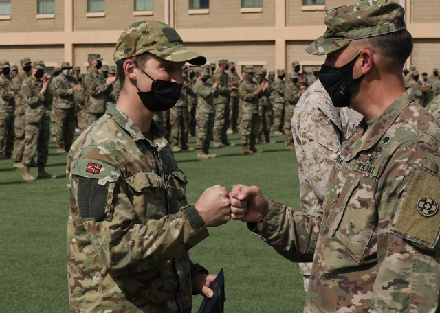 Norwegian Army 1st Lt. Havard Boge fist bumps Army Reserve Brig. Gen. Justin Swanson, the commanding general of the 310th Sustainment Command (Expeditionary) during the March 21, 2021 recognition ceremony at Camp Arifjan, Kuwait, for the 328 U.S. and coalition military personnel who earned the Norwegian Foot March badge. Boge, who represented the Norwegian Army at the ceremony, finished 18.6-mile course with a 25-pound ruck with the second fastest time when he crossed the finish line at 2 hours and 54 minutes. (U.S. Army photo by Staff Sgt. Neil W. McCabe)