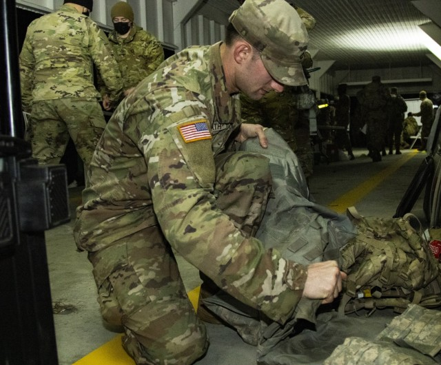 Pfc. Sterling Harvath, an infantryman with 5th Battalion, 20th Infantry Regiment, 2-1 Stryker Brigade Combat Team, checks his rucksack prior to the Norwegian Foot March on Joint Base Lewis-McChord, Wash., Mar. 19, 2021. Participants inspected their rucksacks to make sure the weight was distributed in a manner that would minimize aches and pains along the route. (U.S. Army photo by Spc. Richard Carlisi)