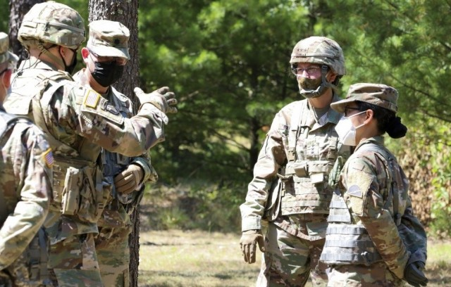 Lt. Gen. Jody J. Daniels, chief of Army Reserve, center right, listens as Brig. Gen. Walter M. Duzzny, left with hand raised, discusses the training successes his Soldiers have witnessed during Operation Ready Warrior at Fort McCoy, Wis., Aug. 19, 2020.