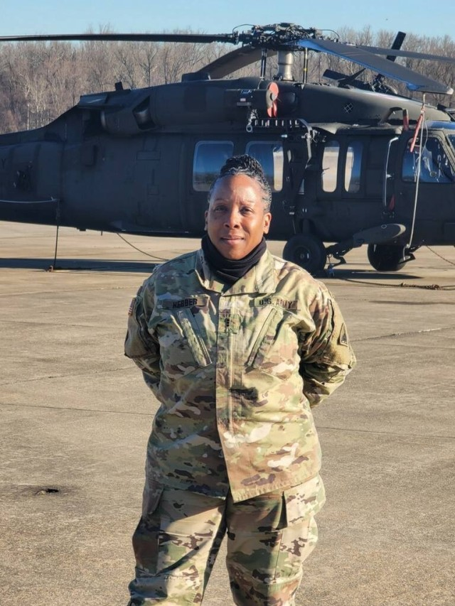 U.S. Army Chief Warrant Officer 4 Melinda Herder, District of Columbia National Guard, stands with helicopters on the flight line at Davison Army Airfield, Ft. Belvoir, Virginia. Herder is the facility maintenance officer at the D.C. National Guard Army Aviation Support Facility. (photo courtesy of Melinda Herder)