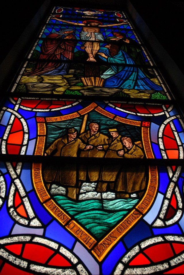 Stained glass windows in Pioneer Chapel feature a Biblical scene in the center with a related symbol or scene of contemporary life below and the Lamp of Knowledge above. This window depicts sacrifice — Christ on the cross and Lieutenants George Fox, Alexander Goode, John Washington and Clark Poling — the four Army chaplains who gave their life jackets and their lives when the Dorchester was sunk in 1943. The Crucifixion window was donated by the Army chief of chaplains in 1967 and dedicated to the graduates of the Command and General Staff College who have died in combat. Photo by Prudence Siebert/Fort Leavenworth Lamp