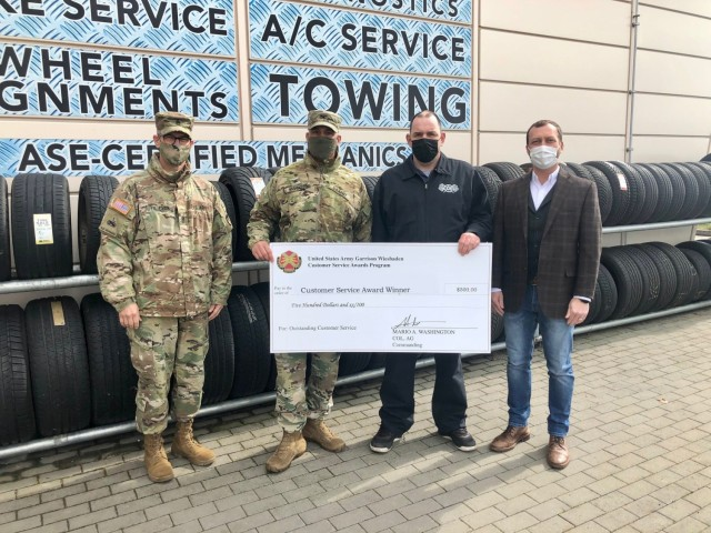 WIESBADEN, Germany -- Steffen Schwenke, Auto Skills recreation assistant, receives his check from Col. Mario Washington, garrison commander, Command Sgt. Maj. Christopher Truchon and Scott Mowry, deputy to the garrison commander, for outstanding customer service at U.S. Army Garrison Wiesbaden March 19, 2021.