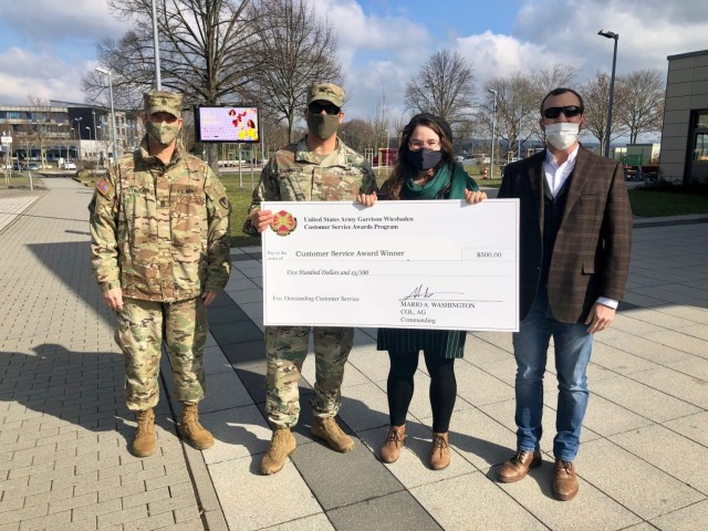 WIESBADEN, Germany -- Katrina Pennington, bartender, receives her check from Col. Mario Washington, garrison commander, Command Sgt. Maj. Christopher Truchon and Scott Mowry, deputy to the garrison commander, for outstanding customer service at U.S. Army Garrison Wiesbaden March 19, 2021.