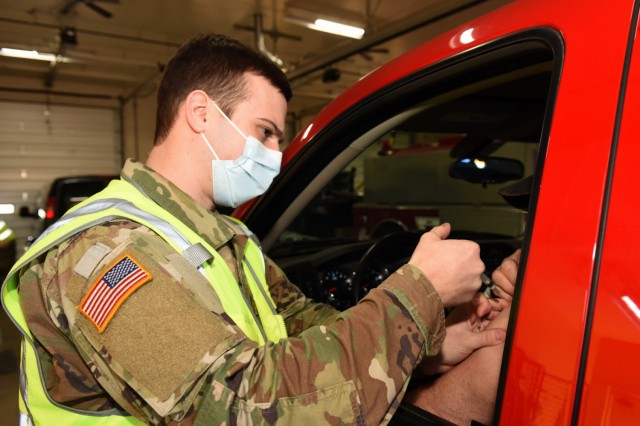 A Michigan Army National Guard Soldier with the Task Force North COVID-19 Vaccination/Testing Team (CVTT) vaccinates members of the community at the Grayling Fire Department, Grayling, Michigan, March 13, 2021. Guard members are helping local health officials get Michiganders vaccinated. (U.S. Air National Guard photo by Master Sgt. David Kujawa)