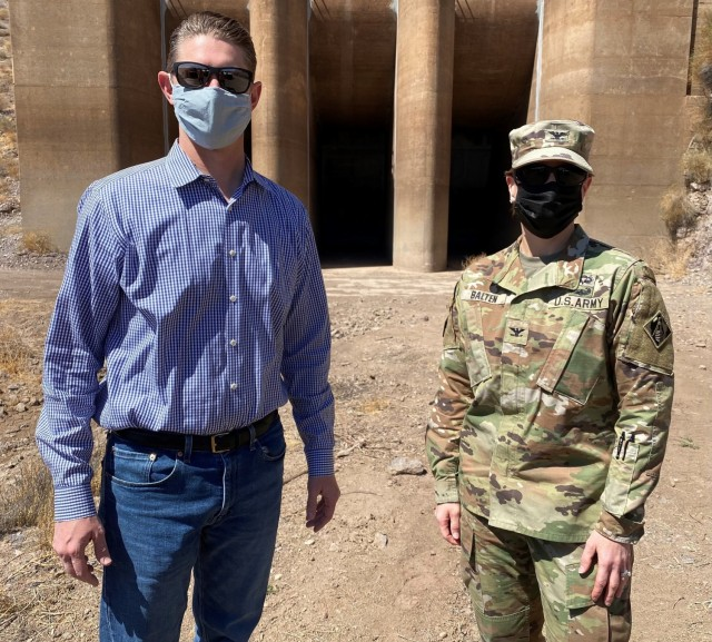Col. Julie Balten, commander of the U.S. Army Corps of Engineers Los Angeles District, right, and David Van Dorpe, deputy district engineer for the LA District, left, visit Painted Rock Dam March 24 near Gila Bend, Arizona. The inflow gates, pictured behind Balten and Van Dorpe, regulate the amount of river water released downstream.