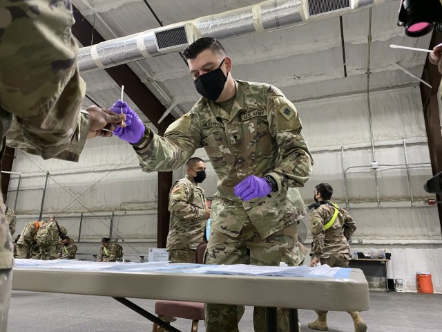 Spc. Andrew Running, a medic with Headquarters and Headquarters Company, 1st General Support Aviation Battalion, 168th Aviation Regiment (GSAB), collects samples for the BINAX test, March 16, 2021 at North Fort Hood, Texas. The Soldiers of Task Force Phoenix have been tested frequently for COVID-19 during pre-deployment training at the fort. (U.S. Army National Guard photo by Sgt. 1st Class Ryan Sheldon)
