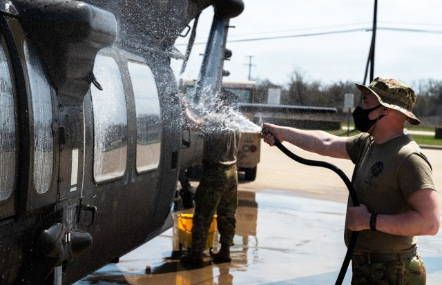 Sgt. Mark Mullen, a crew chief with Charlie Company, 1st Assault Helicopter Battalion, 140th Aviation Regiment, sprays down a UH-60 Black Hawk at the wash rack, Mar. 24, 2021 at Longhorn Auxiliary Landing Strip, North Fort Hood, Texas. (U.S. Army National Guard photo by Spc. Oran Pellissier)