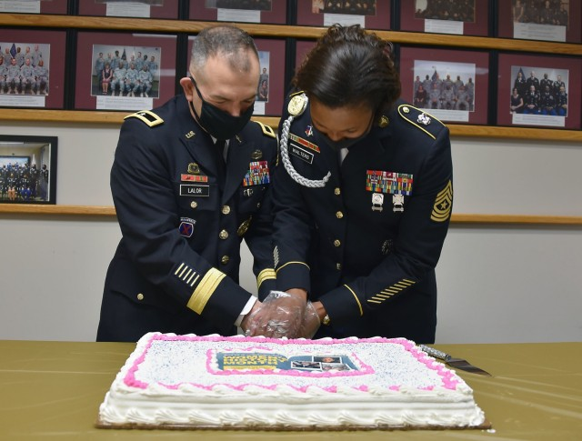 Brig. Gen. Michael Lalor, commander of U.S. Army Medical Logistics Command, and AMLC Sgt. Maj. Danyell Walters cut a cake to celebrate Women's History Month following a commemoration event March 26 at Fort Detrick, Maryland.