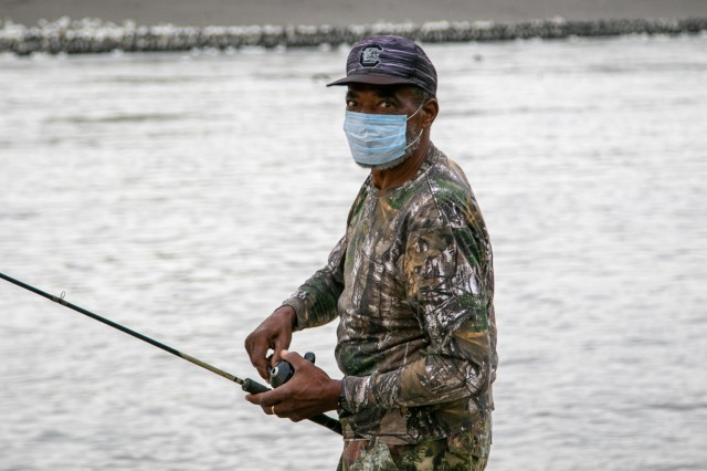 Man with a mask is fishing