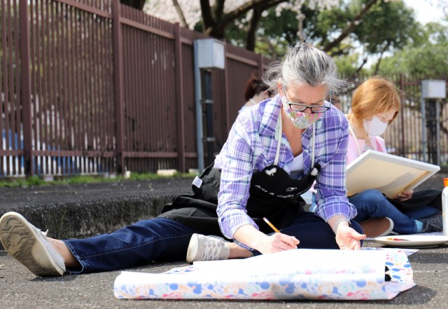 Bree Dalton creates a cherry blossom painting next to the Community Recreation Center at Camp Zama, Japan, March 27.