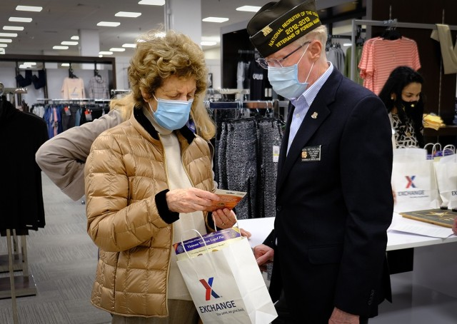 Master Sgt. (Ret.) Ron Reynolds, a VFW Post 8862 service officer, gives Vietnam Veteran widow Carmen Quinn a gift bag courtesy of The Exchange. It included discounts and commissary gift cards during Vietnam War Recognition Day, March 29, 2021 in Vicenza, Italy.
