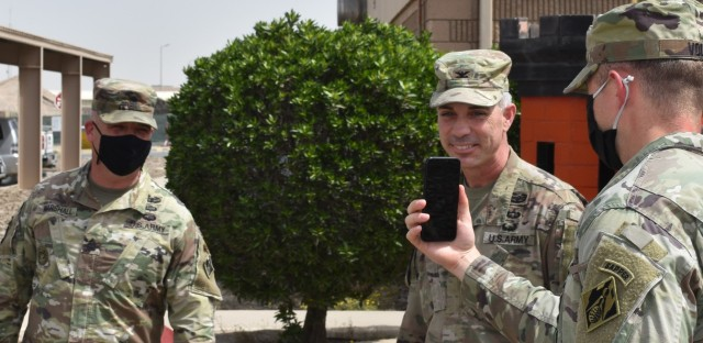 Col. Mark Geraldi smiles as he surprises his outgoing Sergeant Major, SGM Nathan Marshall with the virtual attendance of his family during his awards ceremony at Camp Arifjan, Kuwait. (Photo by Rick Benoit)