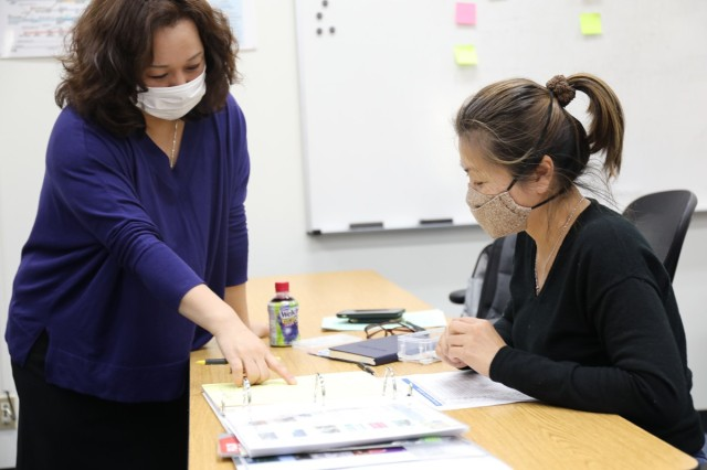 """Megumi Saito, """"Head Start"""" program instructor, teaches participant Yuliana Chang about Japanese culture March 16 at the Camp Zama Education Center. The Head Start program went on hiatus in the spring of 2020 due to the COVID-19 pandemic, before resuming in July that year for Soldier and civilian sponsors only. The February class marked the return of the spouse-specific program, with measures in place to adhere to group-size and social-distancing regulations."""