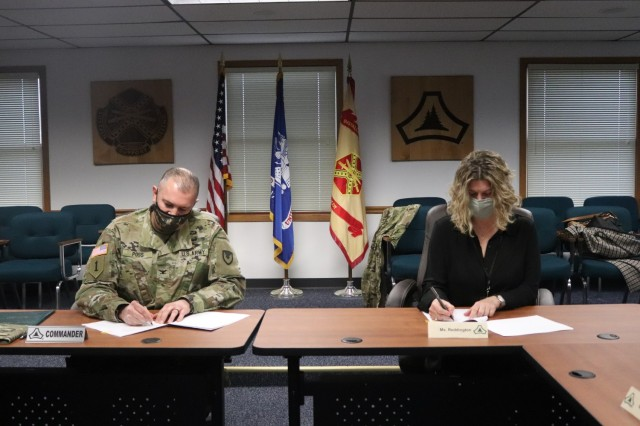 Garrison Commander Col. Michael Poss and Vernon County Administrator Cari Reddington sign an intergovernmental service agreement (IGSA) between the post and Vernon County on March 15, 2021, at Fort McCoy, Wis. The agreement involves line striping on roadways at Fort McCoy and is estimated to save the installation more than $166,000 over the next 10 years. It is the second IGSA the post has made in the last two years. (U.S. Army Photo by Scott T. Sturkol, Public Affairs Office, Fort McCoy, Wis.)