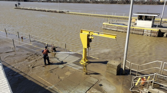 Even after flood waters have receded, crew members have to spray down mud and clear debris at the Locks and Dams 3 on the Monongahela River in Elizabeth, Pennsylvania, March 2, 2021. The cleanup can often take two weeks after a flood. High water from snow melts and extended rain affected the U.S. Army Corps of Engineers Pittsburgh District on the Monongahela River in early March. Elizabeth Locks and Dams (L/D 3) was taken out of service as water entered the operating machinery and topped the lock walls. The average time of high-water stopping operation was 30 hours. The lock staff cleared mud and debris, and each lock was returned to service within eight hours of water receding. Elizabeth is one of the oldest functioning locks in the nation, 114 years old. (U.S. Army Corps of Engineers Pittsburgh District Photo by Philip Delo)