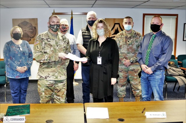(From left) Fort McCoy Resource Management Officer Maureen Richardson, Garrison Commander Col. Michael Poss, Deputy to the Garrison Commander Brad Stewart, Vernon County Highway Commissioner Phil Hewitt, Vernon County Administrator Cari Reddington, Fort McCoy Staff Judge Advocate Lt. Col. Savas Kyriakidis, and Directorate of Public Works Operations and Maintenance Division Chief Nathan Sobojinski were all on hand for the signing of an intergovernmental service agreement (IGSA) between the post and Vernon County on March 15, 2021, at Fort McCoy, Wis. The agreement involves line striping on roadways at Fort McCoy and is estimated to save the installation more than $166,000 over the next 10 years. It is the second IGSA the post has made in the last two years. (U.S. Army Photo by Scott T. Sturkol, Public Affairs Office, Fort McCoy, Wis.)