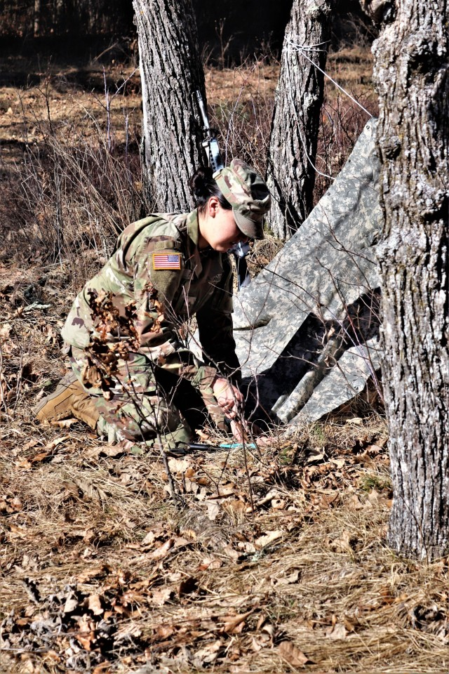 A woman and student in Cold-Weather Operations Course class 21-05 student participates in shelter building training March 11, 2021, at Fort McCoy, Wis. CWOC students are trained on a variety of cold-weather subjects, including snowshoe training and skiing as well as how to use ahkio sleds and other gear. Training also focuses on terrain and weather analysis, risk management, cold-weather clothing, developing winter fighting positions in the field, camouflage and concealment, and numerous other areas that are important to know in order to survive and operate in a cold-weather environment. The training is coordinated through the Directorate of Plans, Training, Mobilization and Security at Fort McCoy. (Photo by Scott Sturkol, Fort McCoy Public Affairs Office)
