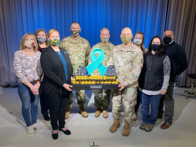 Members of the Directorate of Plans, Training, Mobilization and Security; Fort McCoy, Wis., garrison command team; and installation SHARP employees pose March 10, 2021, with an award given to DPTMS team members for walking almost 150 miles during the #notjustapril SHARP virtual walk held in September 2020. Community members walked a total of 478 miles to show support for sexual-assault survivors.