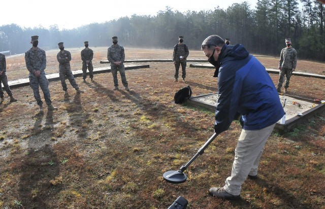 Marty DuMond, Humanitarian Demining Training Center instructor, briefs military members on basic metal detector operations March 25 at Fort Lee's Training Area 4.