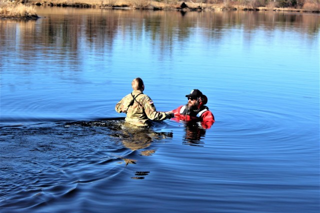 A student in Fort McCoy Cold-Weather Operations Course (CWOC) class 21-05 participates in cold-water immersion training March 19, 2021, at Big Sandy Lake on South Post at Fort McCoy, Wis. CWOC students are trained on a variety of cold-weather subjects, including snowshoe training and skiing as well as how to use ahkio sleds and other gear. Training also focuses on terrain and weather analysis, risk management, cold-weather clothing, developing winter fighting positions in the field, camouflage and concealment, and numerous other areas that are important to know in order to survive and operate in a cold-weather environment. The training is coordinated through the Directorate of Plans, Training, Mobilization and Security at Fort McCoy. (Photo by Scott Sturkol, Fort McCoy Public Affairs Office)