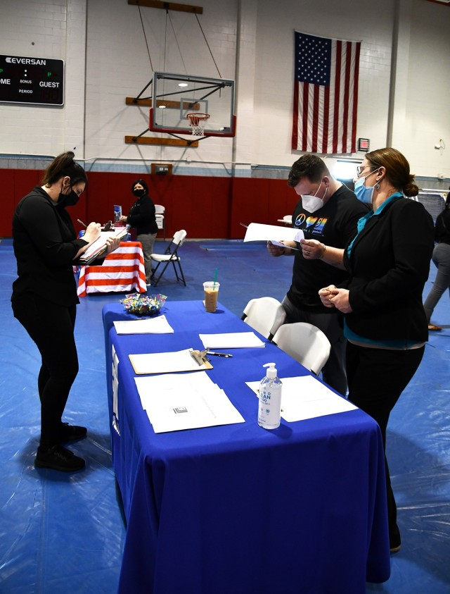 Alizabeth Cannon (left), a military dependent, fills out an application to work at Goodwill as Paul Dunham (middle), Goodwill donation service attendant, and Victoria Sitting, Goodwill assistant manager, stand ready to answer questions.