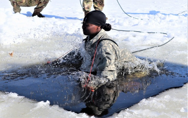 Airman 1st Class Alexis Edwards with the 164th Security Forces Squadron at Memphis Air National Guard Base, Tenn., participates in cold-water immersion training Feb. 26, 2021, at Big Sandy Lake on South Post at Fort McCoy, Wis. CWOC students are trained on a variety of cold-weather subjects, including snowshoe training and skiing as well as how to use ahkio sleds and other gear. Training also focuses on terrain and weather analysis, risk management, cold-weather clothing, developing winter fighting positions in the field, camouflage and concealment, and numerous other areas that are important to know in order to survive and operate in a cold-weather environment. The training is coordinated through the Directorate of Plans, Training, Mobilization and Security at Fort McCoy. (Photo by Scott Sturkol, Fort McCoy Public Affairs Office)Fort McCoy, Wisconsin, CWOC, cold-weather training