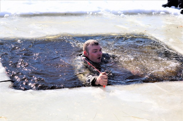 An Airman who is a student in Fort McCoy Cold-Weather Operations Course (CWOC) class 21-04 participates in cold-water immersion training Feb. 26, 2021, at Big Sandy Lake on South Post at Fort McCoy, Wis. CWOC students are trained on a variety of cold-weather subjects, including snowshoe training and skiing as well as how to use ahkio sleds and other gear. Training also focuses on terrain and weather analysis, risk management, cold-weather clothing, developing winter fighting positions in the field, camouflage and concealment, and numerous other areas that are important to know in order to survive and operate in a cold-weather environment. The training is coordinated through the Directorate of Plans, Training, Mobilization and Security at Fort McCoy. (Photo by Scott Sturkol, Fort McCoy Public Affairs Office)