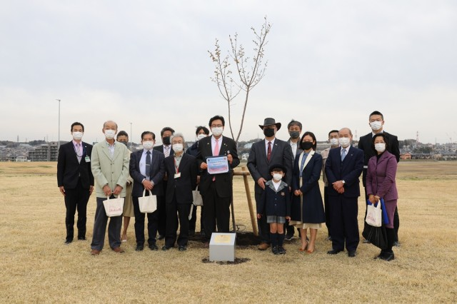 """Representatives from U.S. Army Garrison Japan and Kanagawa City's Chuo Ward pose for a photo the two groups planted a cherry blossom tree together March 25 on a shared area of Sagami General Depot to symbolize a commitment to the friendship between the installation and the city in which it resides. The tree was one of 60 the Chuo Ward donated that were planted on Sagami Depot's """"joint-use"""" area."""