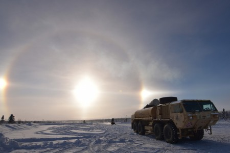 A fuel truck and snow machines prepare for Exercise Arctic Warrior 21 at Donnelly Drop Zone, Alaska, Feb. 8, 2021. The cold-weather training event incorporates airborne operations, situational training and live-fire exercises.