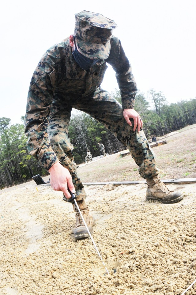Cpl. Joshua Kuplesky, 1st Combat Engineer Battalion, Camp Pendleton, Calif., uses a probe to check the ground surface for planted dummy explosives during training conducted March 25 by the Humanitarian Demining Training Center at Fort Lee.