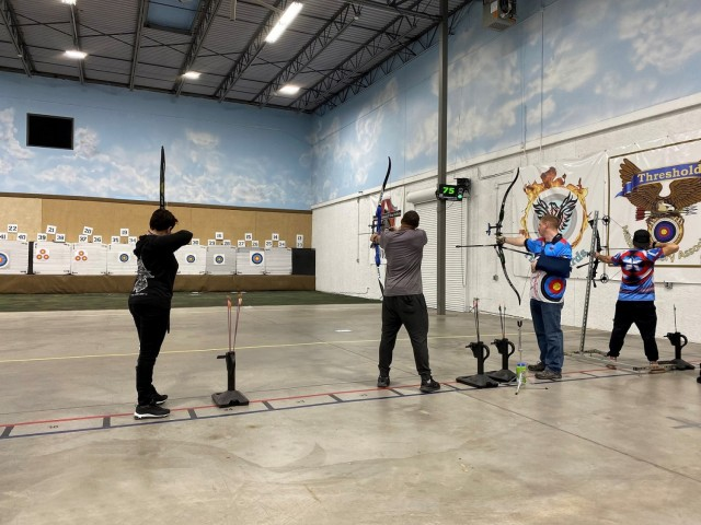 Maj. Adriana de Julio (left), Sgt. Brandon Jenkins (center left), Maj. Kyle Eldridge (center right) and veteran Mike Murphy (right) shoot at targets at the Archery School of the Rockies on March 11, 2021. Army Trials athlete de Julio competed in archery, air rifle and cycling events in the 2021 Army Trials. (Photo courtesy of Courtney Medeiros)