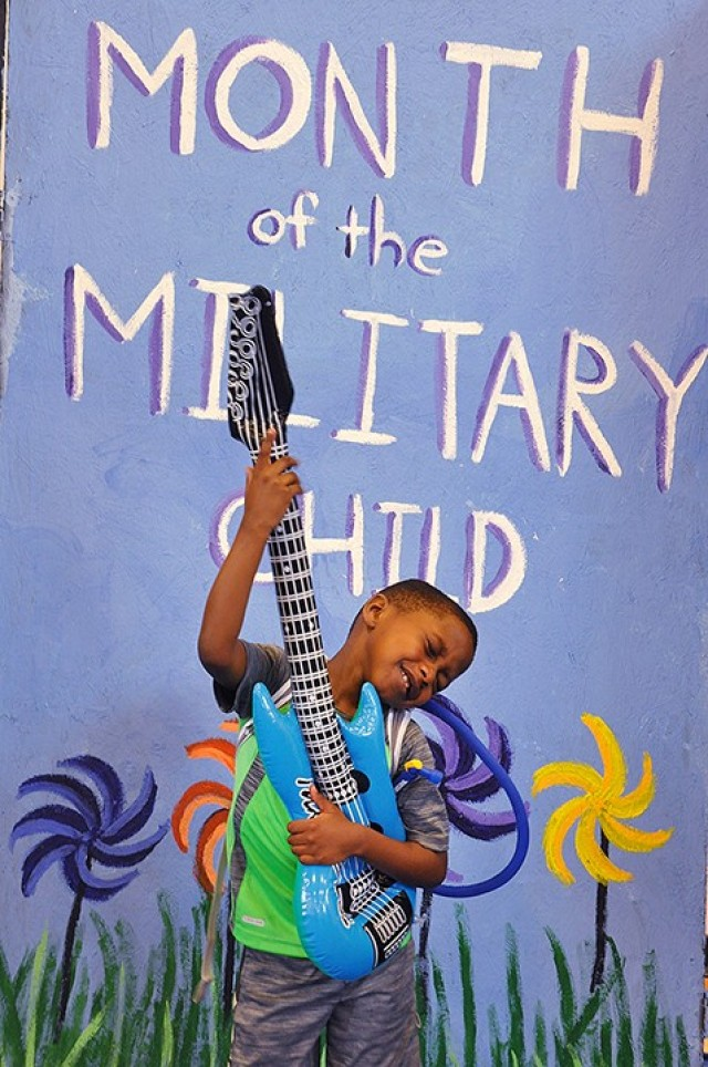 Six-year-old Jonathan Baptiste jams on an inflatable guitar while his mother, Maj. Mona Baptiste, Academic and Technology Support Directorate, Command and General Staff College, takes a video of his performance at a prop photo booth at the Children's Festival April 8, 2017, at Harney Sports Complex. April is Month of the Military Child. File photo by Prudence Siebert/Fort Leavenworth Lamp