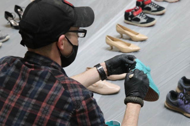 A volunteer paints a pair of shoes teal March 19 at Fort Carson in preparation for a Sexual Assault Awareness Prevention Month display. (Photo by Capt. Jason Elmore)
