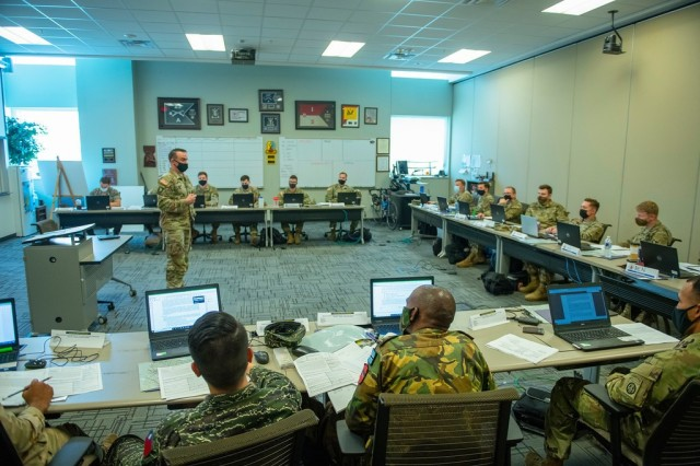 FORT BENNING, Ga. – Capt. Patrick Watts (standing), a member of the training cadre of Fort Benning's Maneuver Captain's Career Course (MCCC), leads his students April 1 here in a discussion on the planning of combat operations. MCCC is one of numerous courses through which Fort Benning's U.S. Army Maneuver Center of Excellence trains leaders for the maneuver force. It is also one of the courses that now take part in a classroom discussion of the sexual assault and other issues an independent review panel found last year at Fort Hood, Texas. Various components of MCoE have begun conducting the discussions in their professional military education classes. Watts has thus far led several Fort Hood-related discussions with groups of his students.