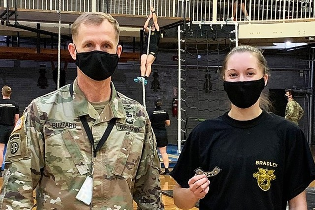 On March 24, Class of 2022 Cadet Elizabeth Bradley shattered the women's Indoor Obstacle Course Test record by six seconds, finishing the course in two minutes and 20 seconds, breaking the previous mark of 2:26 in 2013. She received an IOCT patch from the Commandant of Cadets Brig. Gen. Curtis Buzzard after her run.   		     (Photo courtesy of Col. Nicholas Gist/DPE)