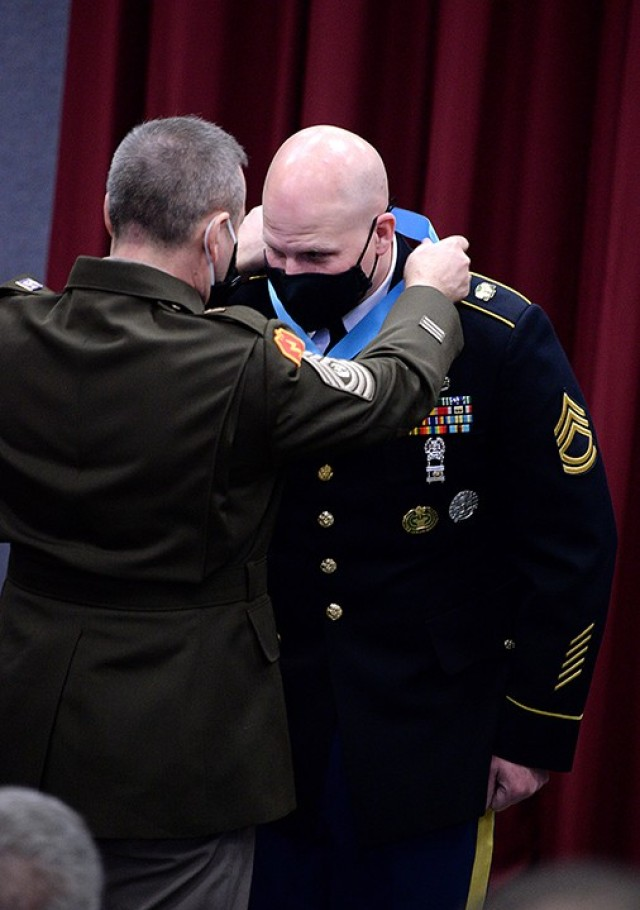 Combined Arms Center Command Sgt. Maj. Eric Dostie places the Sergeant Audie Murphy Club medallion around the neck of Sgt. 1st Class Chad Hickey, 291st Military Police Company, 40th MP Battalion (Detention), during the SAMC induction ceremony for Hickey and Sgt. Anthony Hogan, 256th MP Company, 40th, March 30 in Grant Auditorium. Photo by Prudence Siebert/Fort Leavenworth Lamp