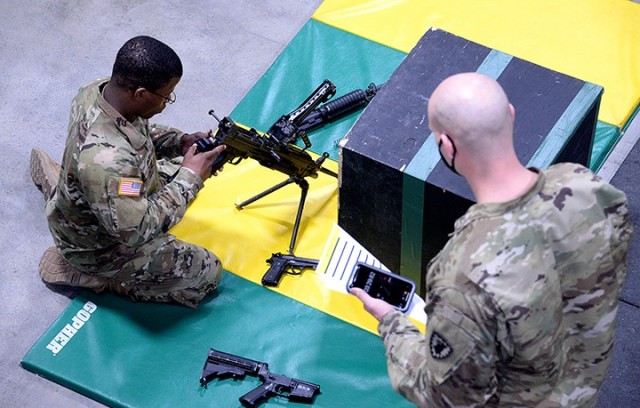 Pfc. Elijah Nash, 526th MP Company, 40th MP Battalion (Detention), assembles and performs function checks on an M4, M9 and M249 under the watch of grader Staff Sgt. Bobby Regan, Headquarters and Headquarters Company, 40th Military Police Battalion (Detention) during the soldier tasks portion of the 15th MP Brigade NCO and Soldier of the Year competition March 24 in the company operations facility. Nash was named Soldier of the Year for the 40th MP Battalion and will go on to represent Fort Leavenworth in the Combined Arms Center competition. Photo by Prudence Siebert/Fort Leavenworth Lamp