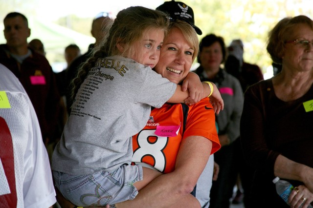 Kerrie Branson, Survivor Outreach Services coordinator for Redstone Arsenal, Alabama, holds Gold Star Family member Kylee Little during a U.S. Army Space and Missile Defense Command-sponsored fall festival at the Huntsville Botanical Gardens on Oct. 18, 2014. Little is the daughter of Spc. Kyle Little, 20, who was killed in action in Salman Pak, Iraq, on May 8, 2007. (U.S. Army photo by Carrie David Campbell)