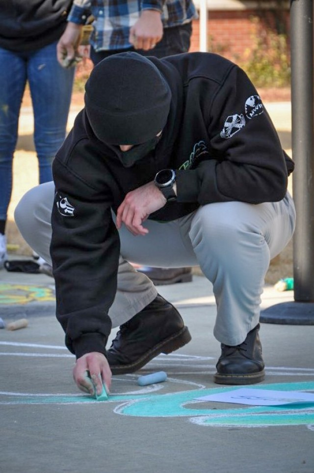CAMP HUMPHREYS, Republic of Korea - Spc. Ian Holmes, the Humphreys Better Opportunities for Single Soldiers (BOSS) President and a CH-47 helicopter repairer assigned to Installation Management Command, helps draw the BOSS logo created as part of their Chalk-Off event, Dec. 4, 2020. The Chalk-Off event was one of the BOSS program's competitions for their Inclusion Cup event, a brigade-level competition taking place over the entire fiscal year 2021, promoting inclusiveness and friendly competition. (Courtesy photo provided by Spc. Ian Holmes)