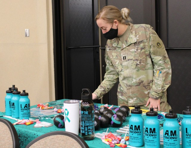 Capt. Nicole McCoy,  Sexual Harassment/Assault Response and Prevention program manager, 1st Theater Sustainment Command, sets up a table with free SHARP gear and information at the Sexual Assault Awareness and Prevention Month kick off event at Olive Theater March 29, 2021 at Fort Knox, Kentucky.
