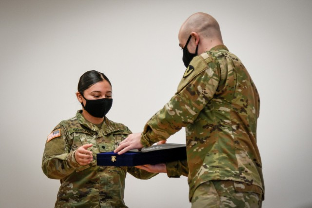 CAMP HUMPHREYS, Republic of Korea - Spc. Ian Holmes, the Humphreys Better Opportunities for Single Soldiers (BOSS) President and a CH-47 helicopter repairer assigned to Installation Management Command, right, presents a commemorative plaque to Spc. Raquel Siguenza, a patient administration specialist assigned to U.S. Army Medical Command, for winning the BOSS Representative of the Month for February 2021, at an awards ceremony here, March 24. The Humphreys BOSS program depends upon the dedicated work of their representatives to ensure that interesting, varied and beneficial programming and events are provided to single and unaccompanied Soldiers throughout Humphreys. (U.S. Army photo by Spc. Matthew Marcellus)