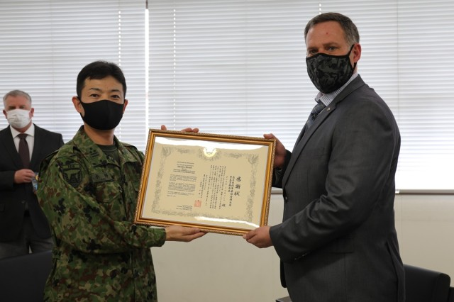 "Daniel Brush, right, U.S. Army Garrison Japan Directorate Emergency Services director, poses with a certificate of appreciation he received from Col. Kazuya Ono, left, commander of the JGSDF's 4th Engineer Group and JGSDF Camp Zama during a March 30 ceremony on Camp Zama, Japan. Brush and four other USAG Japan employees were recognized for their ""continuous cooperation and support to the JGSDF."""