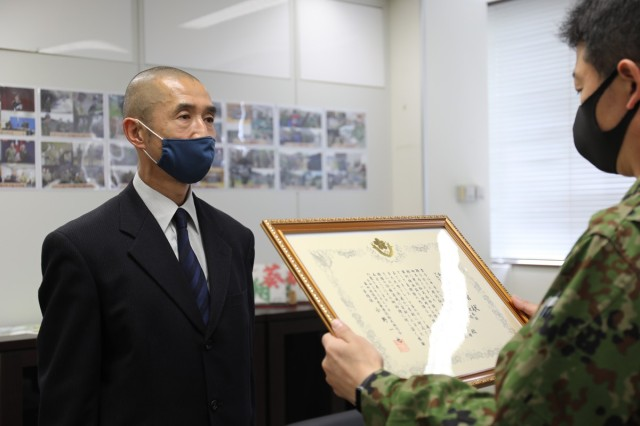 "Yoshihiro Isono, left, assigned to the U.S. Army Garrison Japan Directorate of Plans, Training, Mobilization and Security, receives a certificate of appreciation from Col. Kazuya Ono, commander of the JGSDF's 4th Engineer Group and JGSDF Camp Zama during a March 30 ceremony on Camp Zama, Japan. Isono and four other USAG Japan employees were recognized for their ""continuous cooperation and support to the JGSDF."""