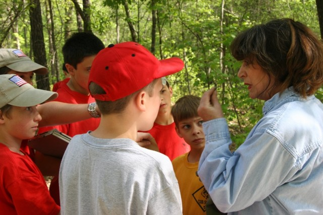 Linda Carnes-McNaughton, program archaeologist and curator, Fort Bragg's Cultural Resources Management Program, Directorate of Public Works, teaches a group of Scouts how to test if an item is ceramic by touching it with their tongue during a public outreach event.