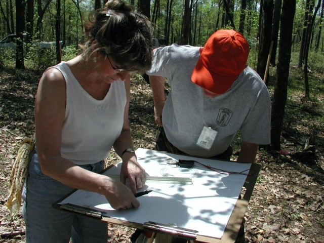Linda Carnes-McNaughton, program archaeologist and curator, Fort Bragg's Cultural Resources Management Program (CRMP), Directorate of Public Works (DPW) and Joe Herbert, former project manager, Fort Bragg's CRMP, DPW, confer in the field while mapping the John Lamont home site, 2005.