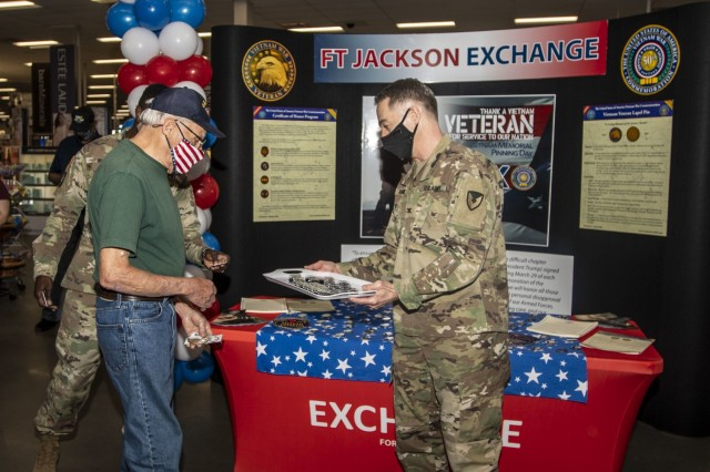 Garrison Commander Col. John 'Wes' Hankins presents Navy veteran Perry Riley with a Vietnam Veteran Lapel Pin March 29 at the Fort Jackson Exchange.