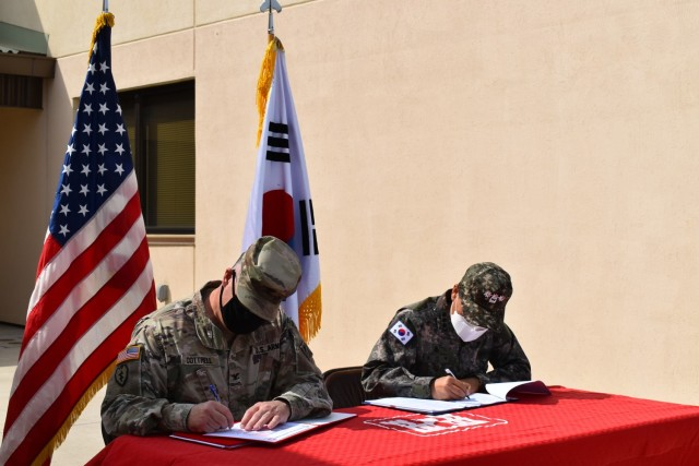 Col. Garrett Cottrell (left), Deputy Commanding Officer - Transformation, U.S. Army Corps of Engineers Far East District, and Col. Pyo In Tae (right), Chief, Program Management Team, ROK Design and Construction Agent, sign the Acceptance Release Letter for SPT060 Site 2 Building E, which will support storage requirements for various agencies across USAG Humphreys, Republic of Korea, Apr. 2, 2021.