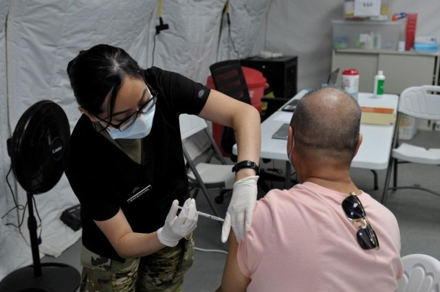 SAIPAN, Northern Mariana Islands (April 3, 2021) – Sgt. Diana Sandoval, assigned to 25th Infantry Division, administers a COVID-19 Vaccine in support of the Commonwealth Healthcare Corporation (CHCC) COVID-19 Vaccination team at the Medical Care and Treatment Site (MCATS). U.S. Indo-Pacific Command, through U.S. Army Pacific, remains committed to providing continued, flexible Department of Defense support to the Federal Emergency Management Agency as part of the whole-of-government response to COVID-19. (U.S. Navy photo by Brad Ruszala)